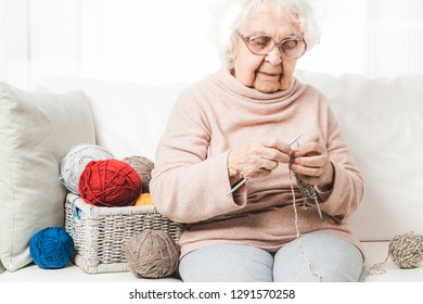 Grandmother knitting with colorful knitting laces balls