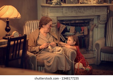 Grandmother is knitting sitting in armchair and her cute little granddaughter is sitting near her. Image with selective focus and toning.