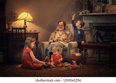 Grandmother is knitting sitting in armchair and her cute little grandchildren are playing on the floor near her.  Image with noise effects, selective focus and toning.