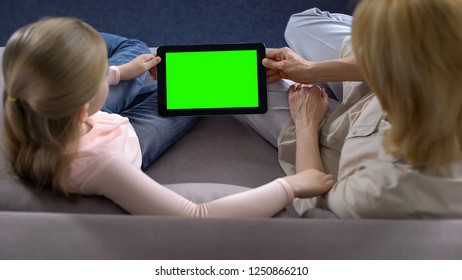 Grandmother and little female grandkid holding tablet with green screen, apps