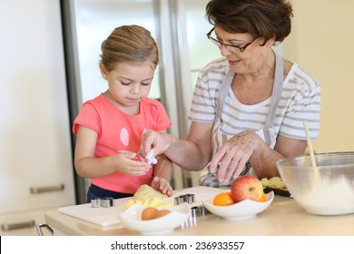 Grandmother with little girl in kitchen baking cookies