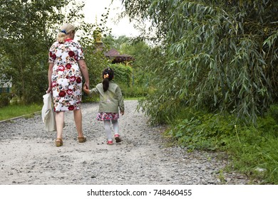 Grandmother and little granddaughter going to church.