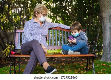 Grandmother and little kid playing with a smartphone in the backyard while wearing protective masks due to coronavirus outbreak