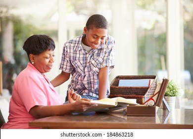 Grandmother Looking At Photo Album With Grandson