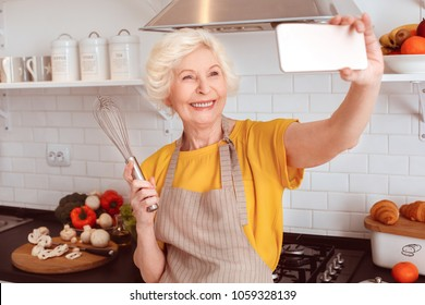 Grandmother makes selfie with a whisk in the kitchen.