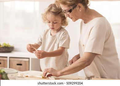 Grandmother making cookies with her grandchild in bright kitchen interior