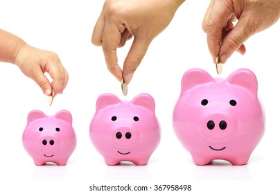 Grandmother, mother, and baby in the family do saving money in pink piggy banks in three different sizes