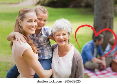 Grandmother mother and daughter with family in background at park against heart