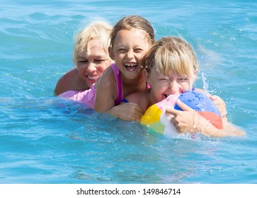 grandmother, mother and granddaughter of fun playing in the water