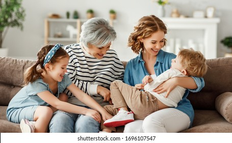 Grandmother and mother hugging and tickling laughing boy while sitting on couch and playing with children on weekend day at home