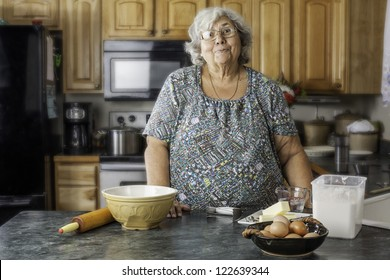 Grandmother or mother in the kitchen by baking supply with a big smile as she gets ready to bake.