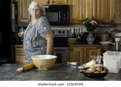 A grandmother or mother in a kitchen looking at supplies getting ready to bake