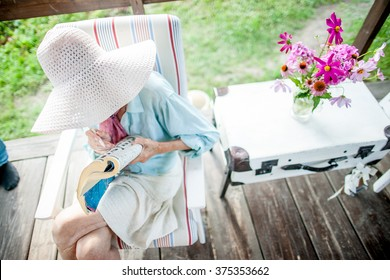 Grandmother. Old woman with a crossword in the garden