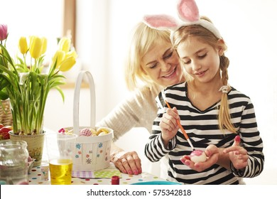 Grandmother painting eggs with granddaughter