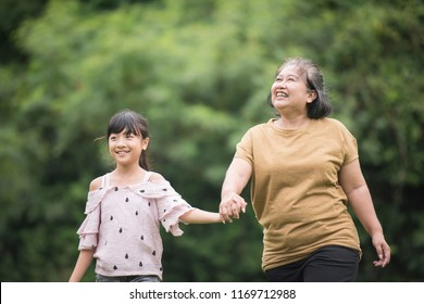 Grandmother Playing With Granddaughter Outdoors At The Park