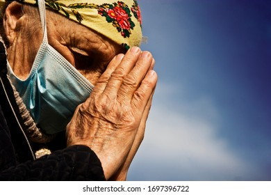 Grandmother praying against a blue sky for healing diseases.Praying old woman because of coronavirus.Grandmother asks for help because of an outbreak of coronavirus infection.