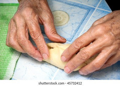 The grandmother prepares pies with a stuffing