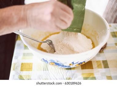 Grandmother preparing batter for pancakes
