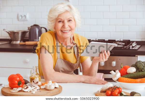 Grandmother preparing salad and watches serial on the tablet
