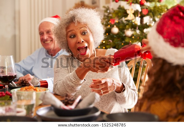 Grandmother Pulling Christmas Cracker With Granddaughter As They Sit For Meal At Table