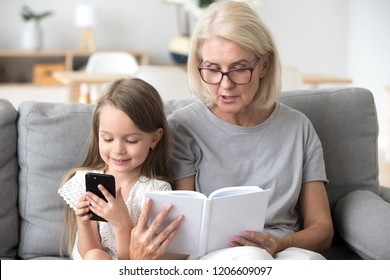 Grandmother read book to little granddaughter interest her in literature, distracted small girl addicted to smartphone play game or watch video on cell, not listening to granny. Generation gap concept