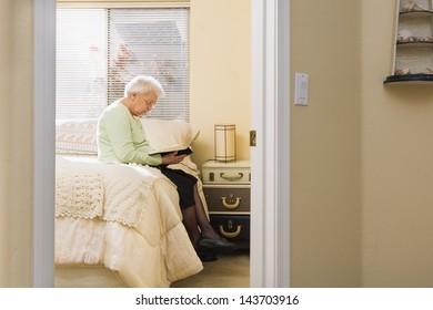 Grandmother Reading Bible in Bedroom (Distant View Through a Door)
