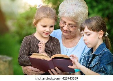 Grandmother reading a book for grandchildren, outdoors