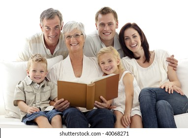 Grandmother reading a book to her children and parents in living-room