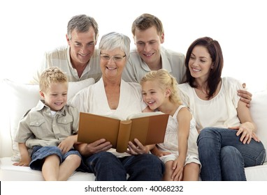 Grandmother reading a book to her family in living-room