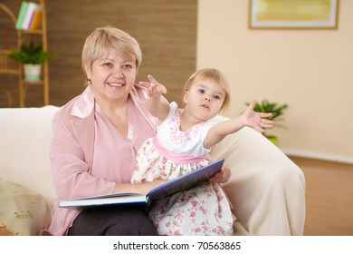 grandmother reading a book to her granddaghter at home