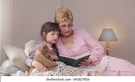Grandmother is reading fairy tale to her little granddaughter