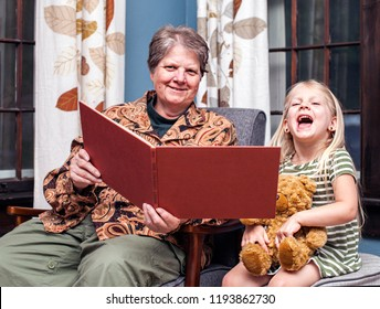 Grandmother reading night  story to her granddaughter at home.