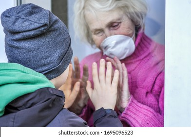 Grandmother in a respiratory mask plays with hands with her grandson through a window. Elderly quarantined, isolated. Pandemic coronavirus covid-19. Caring with older people. Family values