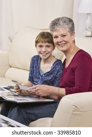 A grandmother is seated on a couch with her granddaughter and they are looking through a wedding album.  They are smiling at the camera.  Vertically framed shot.