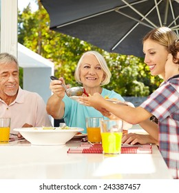 Grandmother serving lunch to grandson at table with a ladle