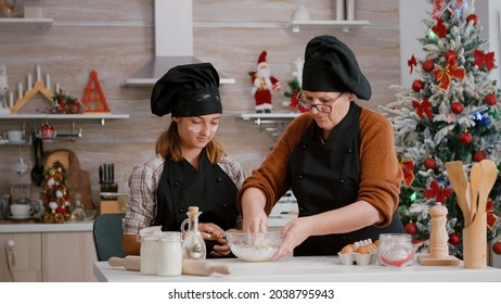 Grandmother showing to grandchild how to prepare traditional cookies dessert enjoying christmastime together. Child wearing apron while making homemade biscuits dough in home kitchen