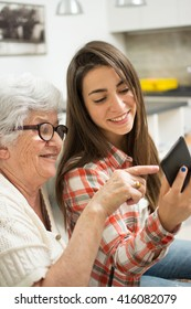 Grandmother showing something on mobile phone to her young granddaughter.