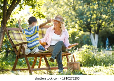 Grandmother sitting in garden and play with her grandson.