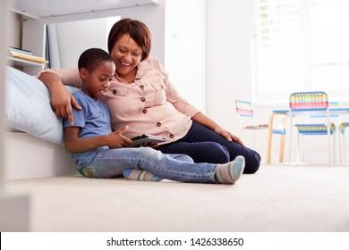 Grandmother Sitting With Grandson In Childs Bedroom Using Digital Tablet Together