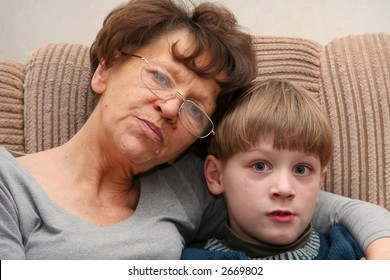 Grandmother sitting on the armchair with her grandchildren