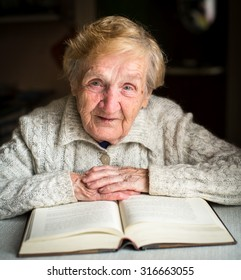 Grandmother sitting at the table with a big book.