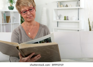 grandmother skimming through family album in lounge