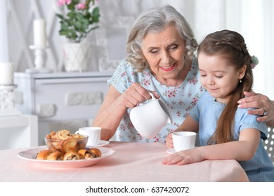 grandmother with a small granddaughter drinking tea
