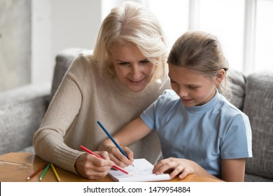 Grandmother spend time at home with granddaughter sit on sofa drawing with colored pencils in album, retired nanny teach little girl help create picture, leisure activity different generations people