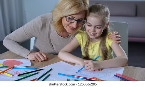 Grandmother spending time with granddaughter and teaching her painting, family