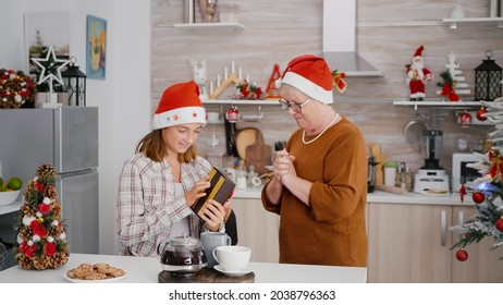 Grandmother surprising grandchild with xmas wrapper gift present celebrating christmastime in decorated kitchen. Happy family enjoying christmas holiday during winter season