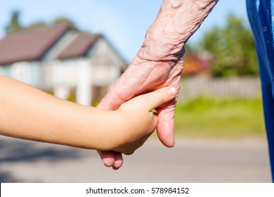 grandmother taking hand of young child, concept