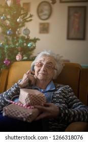 Grandmother talkin g on phone,sitting on sofa.