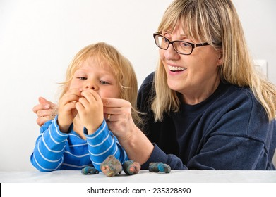 Grandmother teaches her three year old grandson how to play with plasticine. They're happy and laughing together