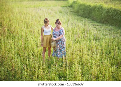 Grandmother teaching her grandchild to find wholesome herbs on a field